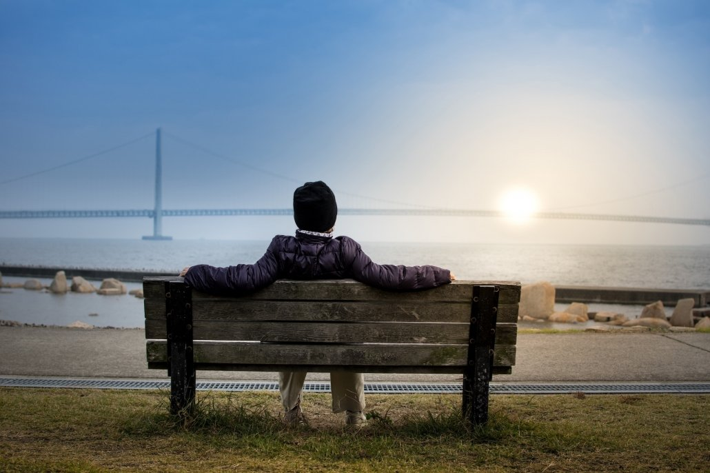 person sitting on bench looking out over horizon survival tactics
