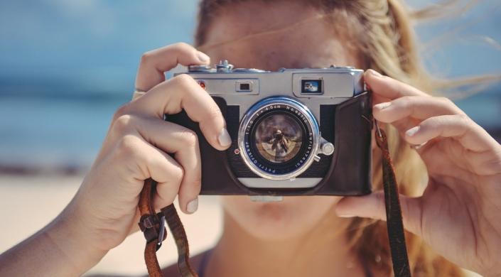 woman looking through camera lens | copyright