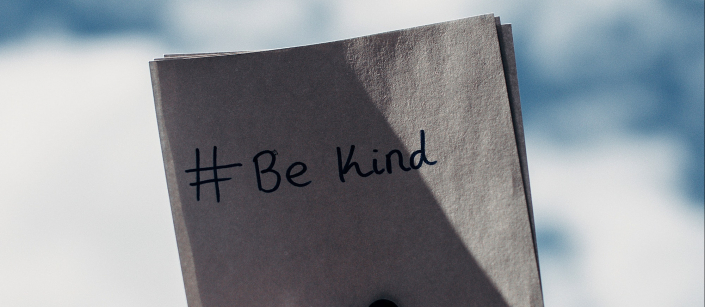 hand holding paper with text be kind social media is hard